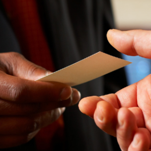 A hand passing a business card to another during networking